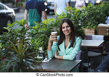 Young beautiful brunette woman sitting in a restaurant