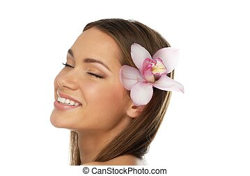 Young beautiful brunette woman with orchid flower