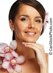 Young beautiful brunette woman with orchid flowers