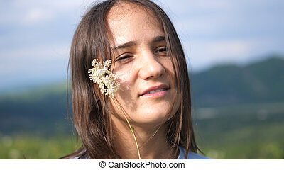 Young beautiful brunette woman with wild flower in the field