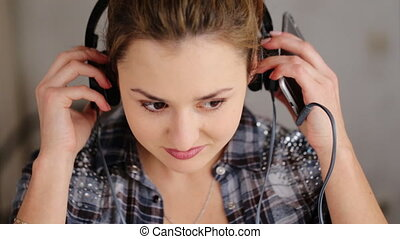 Young beautiful brunettewoman wearing casual style listen music in her headphones at home.