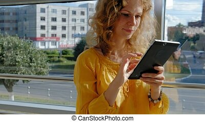 Young beautiful business woman, by the window with a tablet