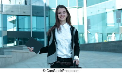 beautiful business woman dancing in the street and smiling