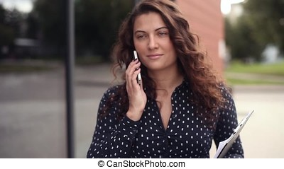 Young beautiful business woman running through the city with documents and talking on the phone with a serious look