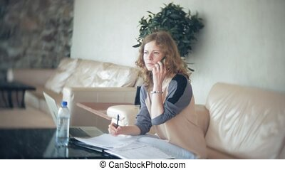 Young beautiful business woman sitting on sofa at table with tablet and using smartphone