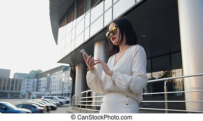 Young beautiful business woman staying outdoors on the street of the city and uses a phone, smiling, feel happy at sunlight, take selfie. Modern woman. White blouse.