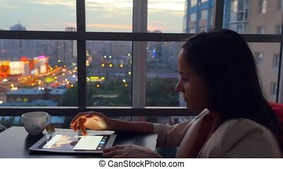 Young beautiful business woman using tablet sitting in a restaurant with amazing view from window on blurred city in lights and bokeh. 1920x1080