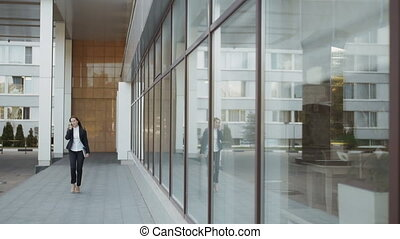 Beautiful Business Woman Walking And Making a Phone Call Outside Business Center