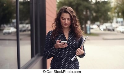 Young beautiful business woman walks next to an office building with documents and talks on the phone while distracted from work