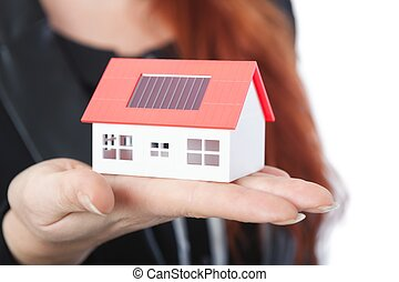 business woman with close up of mini solar house - young...