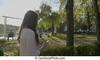 Young beautiful business woman with long hair having a walk in the park and using smartphone in slow motion