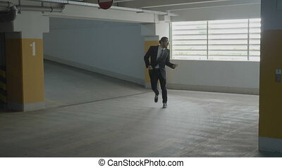 Young beautiful businessman funny dancing and jumping joyfully in a underground parking lot to express his happiness of being promoted