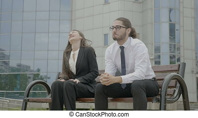 Young beautiful businesswoman and businessman sitting on a bench in front the corporation looking in the eyes bumping fists and dancing