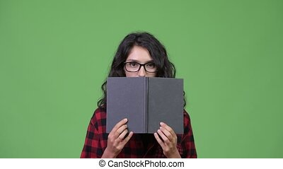 Young beautiful businesswoman covering face with book