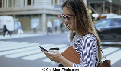 Young beautiful businesswoman holding the documents and coffee cup. Busy female using smartphone standing near the road.
