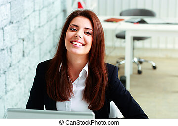 Young beautiful businesswoman laughing in office