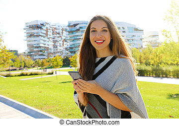 Young beautiful businesswoman smiling and looking at camera while holding mobile phone in her hand.