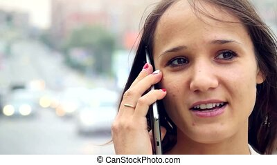 Young beautiful businesswoman using cellphone outdoors while crossing the street in center of the city