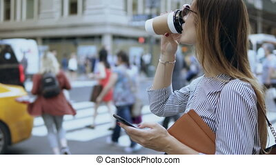 Young beautiful businesswoman using the smartphone near the traffic road. Female holding documents and coffee cup.
