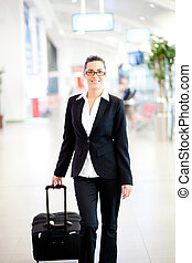 young beautiful businesswoman walking in airport with...