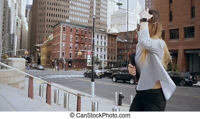 Young beautiful businesswoman walking in financial district...