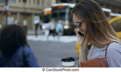 Young beautiful businesswoman with coffee standing on the busy street and talking on smartphone near the road.