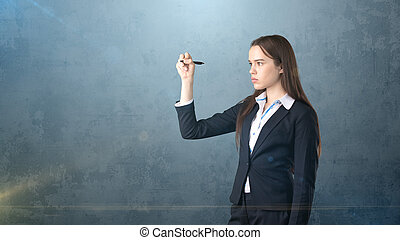 Young beautiful businesswoman with pen writing on the screen.