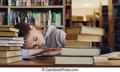 Young beautiful caucasian female student is sleeping on table surrounded by piles of books and papers, phone is lieing in front of her, she is in big university library