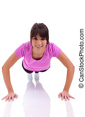 Young beautiful caucasian fitness woman doing push up exercises on floor, isolated on white background