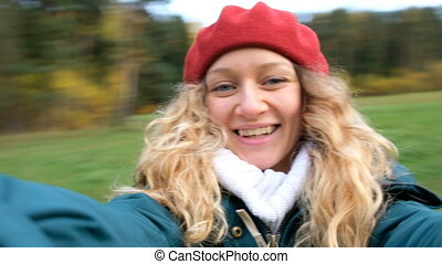 Young beautiful Caucasian girl whirls and shoots himself with a modern camera in autumn forest