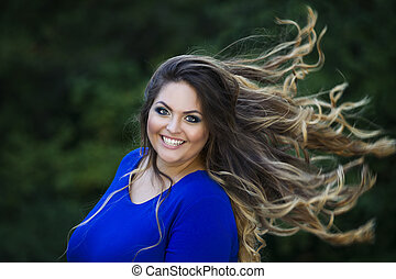 Young beautiful caucasian plus size model in blue dress outdoors, xxl woman on nature with developing in the wind hair