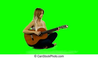 Young beautiful caucasian woman in casual playing guitar. Green screen