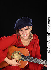 Young beautiful Caucasian woman playing the guitar (Selective Focus, Focus on the face)