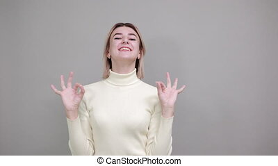 Young beautiful caucasian woman showing ok sign gesture wearing pretty white sweater on isolated gray background