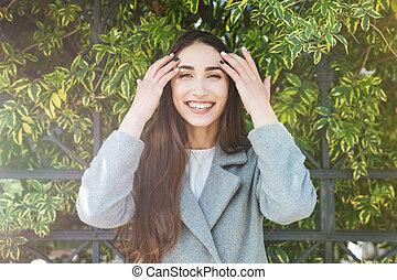 Young beautiful cheerful woman looking at camera