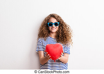Young beautiful cheerful woman with sunglasses in studio, holding red heart.