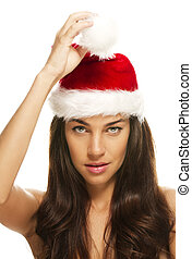 young beautiful christmas woman holding tip of santas hat on white background
