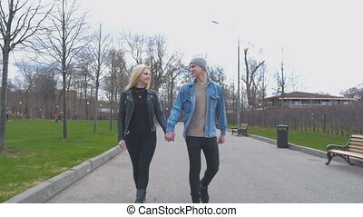 Young beautiful couple, blond and her boyfriend are walking in the park, holding hands. Go to the camera. A beautiful sunny day.