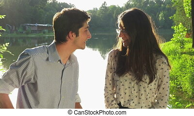 Young beautiful couple chatting and talking at the smartphone in the park