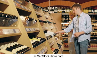 Young Beautiful Couple Choose Wine Using Cellphone In The Supermarket