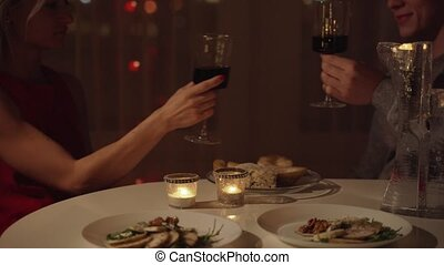 Young beautiful couple having romantic dinner at home