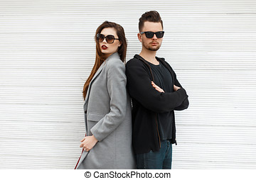 Young beautiful couple in fashionable clothes standing near a white wooden wall.