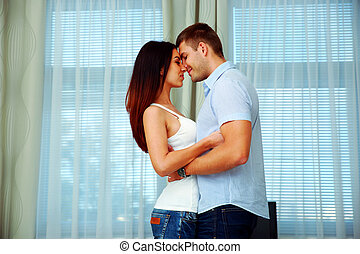 Young beautiful couple in love at home