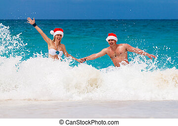 Young beautiful couple in love having fun in the waves ...