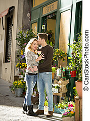 young beautiful  couple in love kissing on street celebrating Valentines day with rose gift