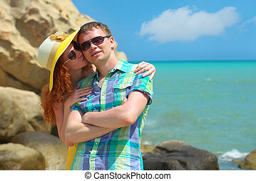 Young beautiful couple in love standing together in sunny coast. Handsome man posing with his redhead girlfriend