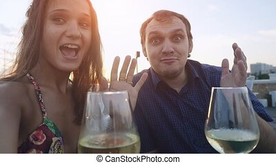 Young beautiful couple in love takes selfie chating with smartphone in outdoor cafe drinking wine at sunset time in slowmotion.