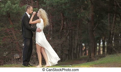 Young beautiful couple in the woods. She softly strokes his face, while  he holding her waist