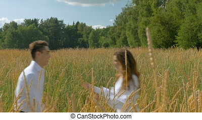 Young beautiful couple in white clothes hugging in on a wheat field