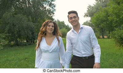 Young beautiful couple is walking in the park. Romantic date. They are happy, laughing and looking at each other.